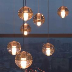 These are the first things that came to mind for your stairwell.  They are pricey, but I think you could create the same effect with something similar.  If the globes were opaque white glass it would also seem less dressy, better for your side entrance. Also very mid century modern!