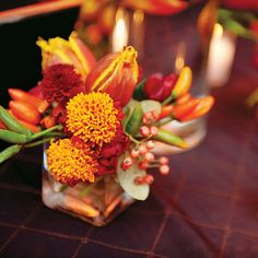 Vibrant Fall Wedding Centerpiece . The wedding reception was held in Old Town at A New Leaf, a modern event space and floral boutique; the venue also provided the wedding's fall-inspired floral arrangements.