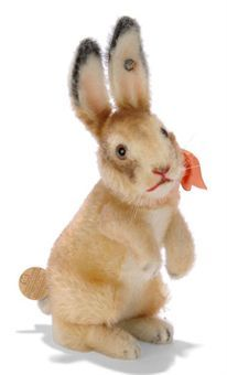 A STEIFF HEAD-TURNING RABBIT, (4318 H), light brown and white mohair, brown and black glass eyes, red stitching, whiskers, wool plush face, ears, arms, feet and tail, tail-operated head-turning mechanism, operating instruction tag on tail and FF button with remains of red cloth tag, circa 1933 --7½in. (19cm.) high (very slight thinning)