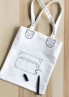 Instructions for sewing your own TOTEBAGS: example - a white tote bag with a hand-drawn pocket and buckles.