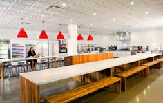 the red pendant lights provide bright pops of colour for the cafeteria while the wooden benches add warmth