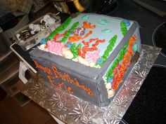 Side view fish tank cake, all decoration made from fondant, except for green seaweed, red and orange coral, buttercream