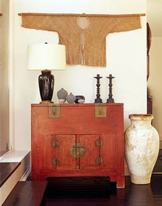 Antique Beijing red lacquer money chest used as a side cabinet in a modern setting.