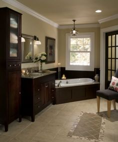 The master bathroom showcases espresso cherry cabinetry and wainscotting. An accent travertine and limestone tile rug adds to the details. Tile and stone from Virginia Tile.