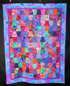 """Beautiful quilt done in all Kaffe Fassett fabrics in the traditional """"Tumbler"""" pattern, but with a new fun twist."""