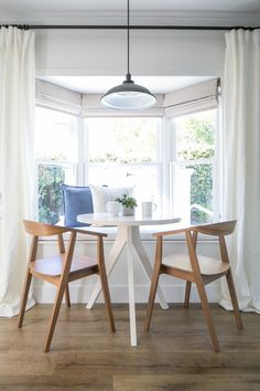 banc de cuisine blanc en face de la fenêtre, table blanche et chaises en bois