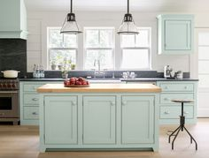 Like the rest of the home, the kitchen is a mix of traditional antiques and metal factory finds. The kitchen island and cabinets are painted a Green Blue that contrasts with the white walls and nature coming through the windows.