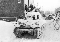 An M4A3 Sherman tank from the 7th Armored Division rumbles through Sankt-Vith after the town was recaptured on 23th january 1945.