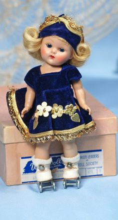 """VOGUE GINNY """"GADABOUT SERIES"""" ROLLER SKATER, MINT-IN-BOX.8"""".Hard plastic, straight-leg strung doll, painted lashes, blue sleep eyes, blonde wig, tagged royal blue skating dress with gilt fringe and floral appliqués, matching panty and hat, white leatherette roller skates, in pink box labeled """"No. 47, Roller Skater, Ryl, B"""".Commentary: Circa 1953, mint-in-box, gorgeous coloring,Van Orman collection."""