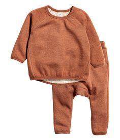 Check this out! BABY EXCLUSIVE/CONSCIOUS. Een sweater en een broek van zachte joggingstof met een gemêleerde structuur. De sweater heeft lange raglanmouwen, een drukknoopsluiting boven en een smalle, geribde boord rond de halsopening, aan de onderkant en onder aan de mouwen. De broek heeft elastiek in de taille, steekzakken en een boord onder aan de pijpen. De set is gemaakt van biologisch katoen.  – Ga naar hm.com om meer te bekijken.