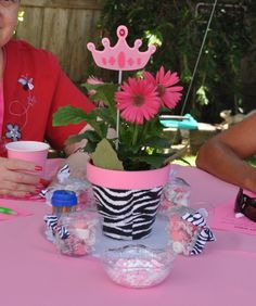 The center pieces - modge podged clay pots and gerbera daisies and painted rims  The favors- clear takeout box filled with pink saltwater taffy, zebro bow and vellum thank you tag