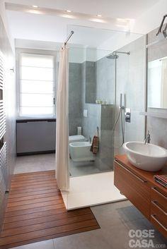 Il bagno viene idealmente suddiviso in tre posizionando il box doccia nel mezzo. Come nella zona giorno, anche qui un controsoffitto, che riproporziona il volume abbassandone l'altezza da 300 a 240 cm, individua le aree funzionali con l'ausilio di luci differenti.