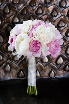 "Bridesmaids carried plush bouquets of peonies and roses in varying shades of pink. The bride's bouquet was ""classic and romantic with a touch of color,"" she said, and included a mix of peonies, gardenias and garden roses."