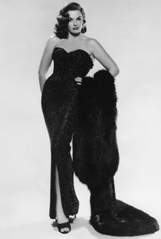 I imagine 'stuck in the past' to be an old  glamorous 50's movie stair who would put on her old gowns and go out on the town to relive her glory I like the dress, and hair (Jane Russel)