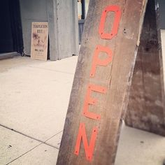 """Our new """"Open"""" sandwich board sign for 2nd Fridays Galley Night event. Made out of reclaimed wood and letters hand cut out of aluminum sheets, painted orange."""