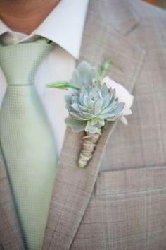 The grooms boutonniere is a combination of ivory spray roses, pale green succulents, and greenery wrapped in raffia.