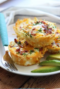 Hash brown egg nests with avocado are crispy hash browns topped with a baked eggs, crumbled bacon and more cheese. Served with chilled avocado slices.