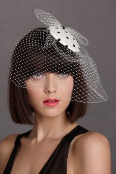 """Guinguette Bibi  $180.00  STYLE: 24184558    Pomp & Ceremony's Parisian pairing of black and white polka-dotted silk and tulle netting makes for a lively adornment with a vintage dance-hall feel. 4.25"""" diameter hat, 10""""L veil with 7""""W bow. Fastens with a comb. Buckram, wire, polyester, silk, metal, tulle. Handmade in Canada."""