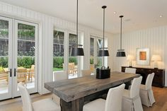 reclaimed timber table + slipcover parsons chairs + pendants in paneled dining design by Pacific Peninsula Group