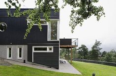 Swedish House With Dark Wooden Exterior And Detached Garage