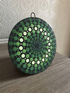 This light weight wooden disk dot mandala was painted with enamel paint in various shades of green. On the back is a leather loop so that it can be hung on the wall. It is six and a half inches wide.