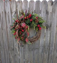In this Christmas and wintertime wreath, a gorgeous wired plaid bow and bundles of loose twine is the focal point. Beautiful greenery, berries, pomegranates, and pine cones create a lovely backdrop. This wreath is perfect for use during Christmas and through winter. This wreaths