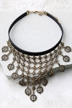 """We're spellbound by the In a Trance Black and Gold Choker Necklace! Layers of antiqued gold charms dangle from a black vegan leather choker. Necklace measures 11"""" long with a 3"""" extender chain."""