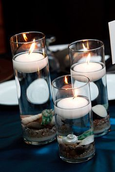 this is neat - floating candles in cylinder vases with white sand & shells...
