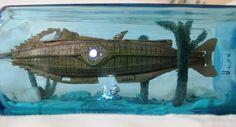 Ubåten Nautilius ur Disneys film från 1954 av Jules Vernes En världsomsegling under havet. Båtens stora fönste upplysta liksom ljuset ner mot dykarna under båten.