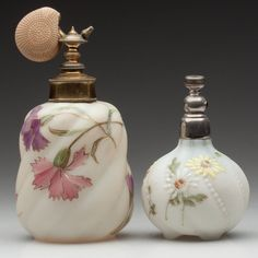 VICTORIAN ART GLASS ATOMIZERS, comprising a Mt. Washington no. 2432 example decorated with yellow and white daises, numbered under base, and an unmarked example with gold-traced polychrome floral decoration, each with metal mounts. Late 19th/early 20th century.$75 - $125