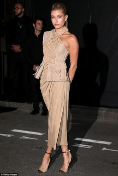 Nude look: Hailey Baldwin wore a quirky midi-dress for the Vogue party, the one-shouldered frock flaunting her toned arms