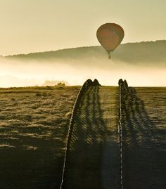 A hot-air balloon drifts through early morning mist at dawn, on a cold October morning. The warm light of the sun, emphasizing the mist and the frost on the fences and fields. Taken at the annual balloon festival outside of Winchester, Virginia