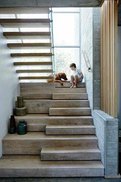 escalier design avec des marches en couleur grisâtre, des murs en gris clair, marches à deux niveaux, plus haut et plus bas, fenêtre haute qui donne sur l'escalier