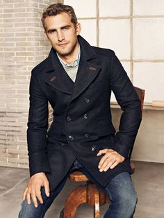 Shop this look on Lookastic:  https://lookastic.com/men/looks/navy-overcoat-grey-crew-neck-sweater-light-blue-long-sleeve-shirt-navy-jeans/6057  — Light Blue Long Sleeve Shirt  — Grey Crew-neck Sweater  — Navy Overcoat  — Navy Jeans