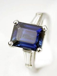 This vintage sapphire engagement ring by J.B.Star pays tribute to a gorgeous sapphire. Measuring 2.79 carats. Set in platinum. @1990 - Tapered baguette cut diamond; 0.38 carats. Emerald cut sapphire; 2.79 carats.