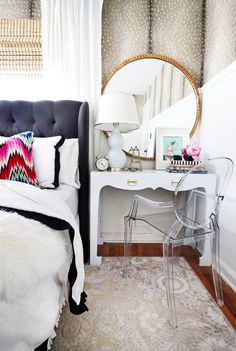 Chic bedroom featuring a chic side table/vanity with a lucite chair and gilded mirror.