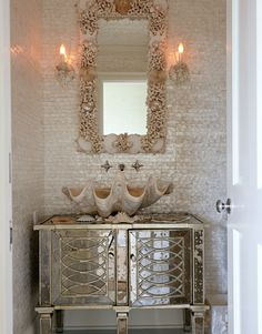 In the powder room, a mirrored vanity, a giant clamshell sink, and a shell mirror are at home with Mother of Pearl tiles.