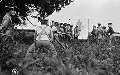 Soldiers at gunnery practice. The soldier in the foreground is crouching behind a tripod, a officer in the background is pointing out hits on a large target, Horsham district, post Horsham, Tripod, Soldiers, World War, Target, Image, Target Audience, Goals