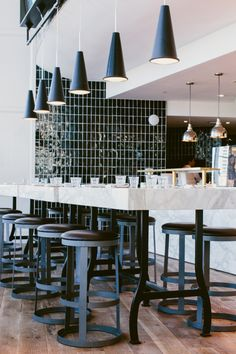 Meyer Davis — St. Cecilia  lights over bar communal table (high top)