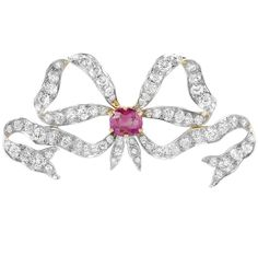 A Belle Epoque Platinum, Gold, Ruby and Diamond Bow Brooch. Centring one cushion-cut ruby approximately 1.50 cts., set throughout with 74 old European and old-mine cut diamonds approximately 5.00 cts., circa 1905. #BelleÉpoque #brooch