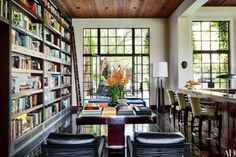 In the Los Angeles home of movie producer Peter Guber and his wife, Tara, the main library is appointed with Minotti armchairs (in the foreground), a custom-made Jean de Merry table, and bookshelves created by the home's interior designer, Nancy Heller.