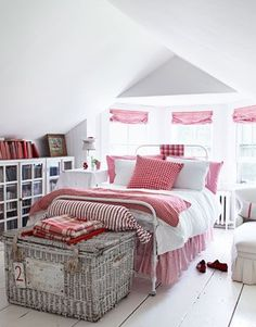 a bed with red and white bedding in the middle of a white room