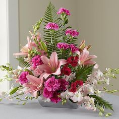 This beautiful, blushing tribute to a life well-lived is an excellent choice for expressing your sympathy.. Handcrafted in gorgeous shades of pink from soft-to-saturated this lovely arrangement includes roses, carnations, Dendrobium orchids, snapdragons and Asiatic lilies accented with graceful greens in a rectangular bowl of brushed silver-tone metallic plastic. It brings a welcome, refreshing note to the solemnity of wakes and funeral services and is bound to be long remembered and…