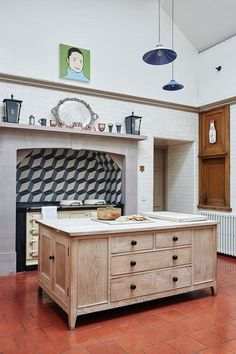 A country kitchen with patterned wall & terracotta floor tiles. An aga and white wooden island. Kitchen design ideas - worktops, cabinets, taps, sinks, lighting from House & Garden.