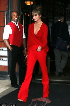 Even the doorman's impressed! Chrissy Teigen turned heads as she left a New York hotel on Thursday dressed in a scarlet red ensemble that flashed a hint of cleavage