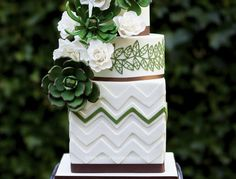 Everything that a traditional wedding cake isn't supposed to be, but everything a cake needs to look fantastic. What one would normally use to decorate, you don't see on this cake. Here the green flowers are the centre of attention. One look at this cake and you're thinking of an afternoon when you're sitting outside and soaking up the sun while the green leaves are rustling in the wind. The succulent and chevron take traditional to another level and the dark green, white and brown colors…