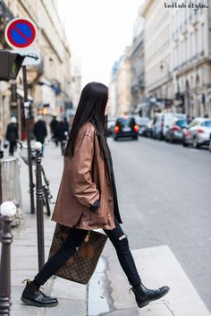 Womenswear Street Style by Ángel Robles. Woman wearing brown leather coat, ripped skinny jeans, ankle boots and Louis Vuitton bag. Fashion Photography from Paris Fashion Week.