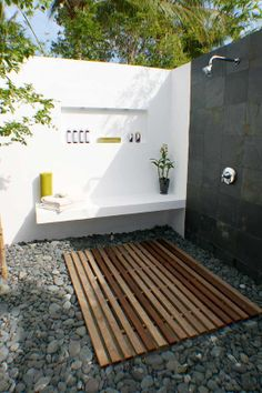 Cool slate meets clean white walls and smooth river stones in this beautiful outdoor shower. A recessed spot to store products and a built-in bench add to the spa vibe.