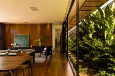 A walled garden filled with tropical plants flanks a glazed hallway at this house in the Brazilian town of Franca influenced by modernist architecture.