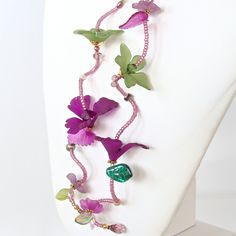 """Lush: Green and Purple Flower Lariat Necklace. This 50"""" lariat necklace of life-like Lucite flowers is the perfect piece for the woman with unique style. Full of rich color and  feminine details, you can wear this beautiful accessory many ways to complement your look. Wearable Art! https://earthandmoondesign.com/products/lush-green-and-purple-flower-necklace"""